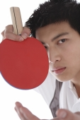 Young man with table tennis paddle, looking at camera - blueduck