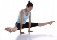 Female gymnast performing gymnastics in studio, balancing on two arms - blueduck