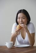 Young woman eating a croissant - Yukmin