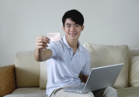 Man sitting on sofa with laptop, holding out credit card - Yukmin