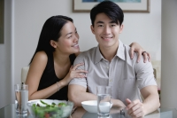 Couple at home, sitting by dining table, man looking at camera - Yukmin