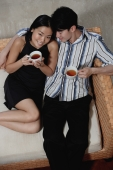 Couple sitting on sofa, holding cups of tea - Yukmin