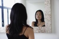 Young woman looking in mirror - Yukmin