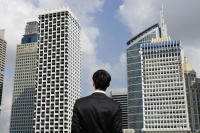 Businessman surrounded by buildings, rear view - Yukmin