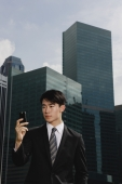 Businessman looking at mobile phone, cityscape in the background - Yukmin
