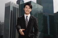 Businessman holding hand out toward camera, buildings in the background - Yukmin