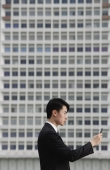 Businessman with mobile phone, side view - Yukmin