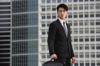Businessman looking at camera, holding briefcase - Yukmin