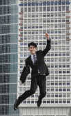 Businessman jumping in air, smiling - Yukmin