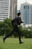 Businessman running through the park - Yukmin