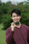 Man holding camera, smiling - Yukmin