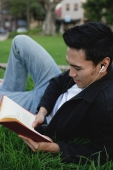College student lying on grass, reading a book - Marcus Mok