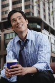 Businessman sitting in the city, holding disposable coffee cup - Marcus Mok