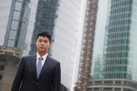 Businessman looking at camera, city location - blueduck