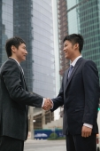 Businessmen in the city, shaking hands - blueduck