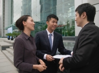 Businessmen and businesswoman outside a building, talking - blueduck