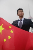 Businessman holding China flag, Oriental Pearl TV Tower in the background - blueduck