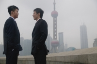 Businessmen talking, Oriental Pearl TV Tower in the background - blueduck