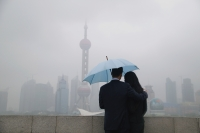 Couple using an umbrella looking at Oriental Pearl TV Tower in the background - blueduck