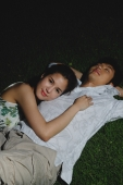 Young couple laying in grass, star gazing - Marcus Mok