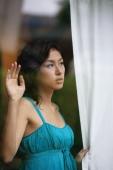 Woman looking through window, holding curtain - Yukmin