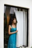 Woman looking out window, holding curtain, wearing dress - Yukmin