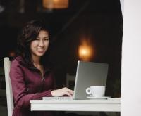 Woman sitting in cafe working on laptop, looking at camera, smiling - Yukmin
