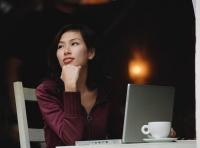 Woman sitting in cafe working on laptop, looking away - Yukmin