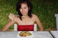 Woman sitting in restaurant eating pasta, looking at camera, smiling - Yukmin