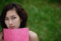 Woman holding pink journal and looking over journal, away from camera - Yukmin