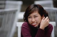 woman sitting at an outdoor cafe, wearing sweater, smiling - Yukmin