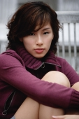 woman sitting with arms wrapped around knees, looking at camera - Yukmin