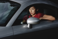 Woman driving car, looking out window at camera - Yukmin