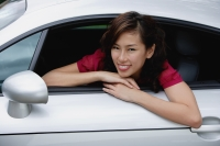 Woman sitting in car, hanging out driver side window, smiling at camera - Yukmin