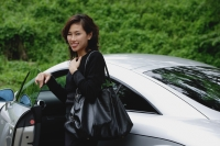 Woman getting into car, smiling at camera - Yukmin