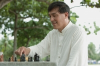 Man playing chess in park - Yukmin