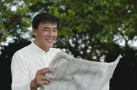 Man sitting in park reading newspaper - Yukmin