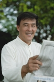 Man sitting in park, reading newspaper, looking at camera - Yukmin