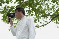 Man in park holding super 8 movie camera - Yukmin