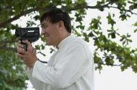 Man in park using super 8 movie camera - Yukmin