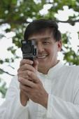 Man in park using super 8 movie camera, looking at camera - Yukmin