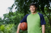 Man playing basketball, holding ball, in park - Yukmin