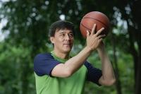 Man playing basketball in park, throwing ball - Yukmin