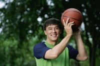 Man playing basketball in park, looking at camera, smiling - Yukmin