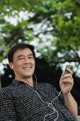 Man sitting in park listening to MP3 player, smiling - Yukmin