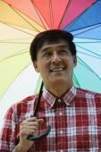 Man standing under rainbow umbrella, smiling - Yukmin