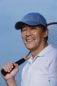 Man holding tennis racket over shoulder, smiling at camera - Yukmin