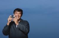 Man holding camera, smiling - Yukmin