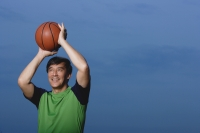 Man playing basketball, throwing ball, smiling - Yukmin