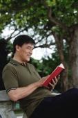 Man sitting on bench in park reading - Yukmin